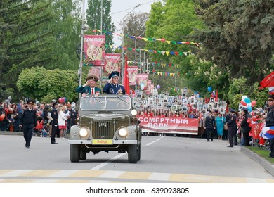 Pyatigorsk, Russia - May 9, 2017: Old UAZ car with veterans is ahead the column Immortal Regiment. Participants column Immortal Regiment bear posters with the image of his relatives died in the battle