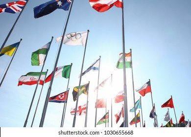 Pyeongchang, South Korea - February 21, 2018: Flags of the participants of the Olympic games in Pyeongchang 2018 against the sky