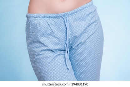 Pyjamas pajamas. Closeup of female legs wearing blue pyjama pants on blue. Pajama party at night. Studio shot.