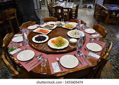 Pyongyang, North Korea - April 29, 2019: Interiors of the restaurant in Pyongyang. Table served with snacks and bottles water in the restaurant