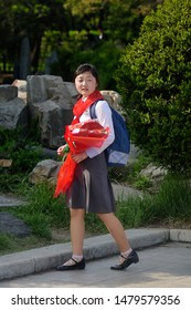 Pyongyang, North Korea - April 29, 2019: Young girl, member of the Korean Children's Union KCU, Young Pioneer Corps, on a city street