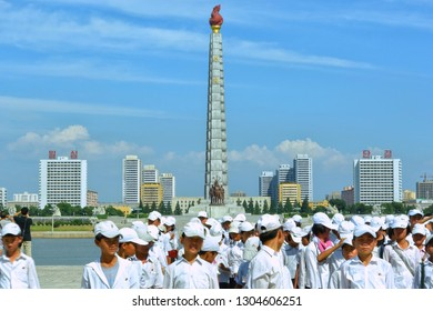 Pyongyang, North Korea - AUG 2012: The students stand on the Kim Il-sung Square, and the landmark building of Juche Tower in Pyongyang