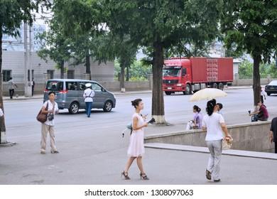 Pyongyang, North Korea - AUG 2012: A beautiful Korean girl walking on the sidewalk near the entrance of Pyongyang Subway