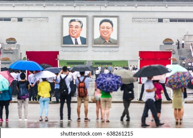 Pyongyang, North Korea - August 15th 2016 - Tourist observe a big group of students practicing an exercise in front of North Korea's  leader pictures.