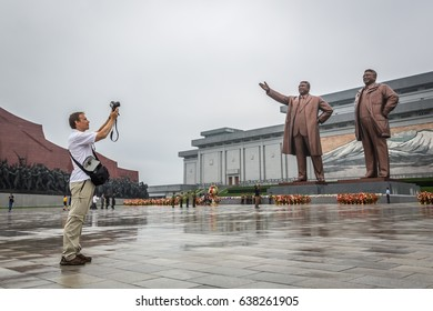 Pyongyang, North Korea - August 15th 2016 - Tourists taking a picture of a big statue in Pyongyang, North Korea capital in a cloudy day.