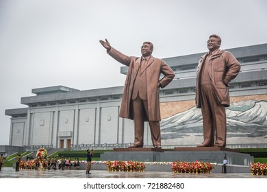 Pyongyang, North Korea - August 15th 2016 - Locals walking in front of a big statue in Pyongyang, North Korea capital in a cloudy day.