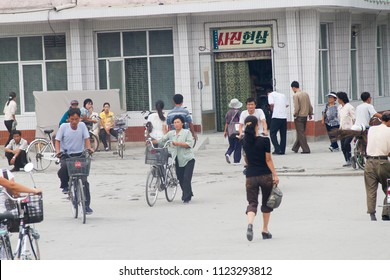 PYONGYANG, NORTH KOREA - AUGUST 27 2013: Citizens passing by and around a photo processing shop on a hectic warm summer day