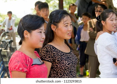 PYONGYANG, NORTH KOREA - AUGUST 27 2013: Young women looking curiously at tourists during a gathering of a local event