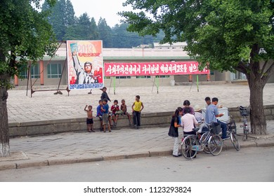 PYONGYANG, NORTH KOREA - AUGUST 27 2013: A young little boy happily waves at tourists in front of an old standing propaganda poster behind him around a crowd