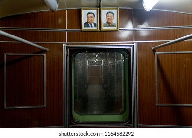 PYONGYANG, NORTH KOREA - AUGUST 27 2013: Framed portraits of Kim Il-sung and Kim Jong-il over the door in an empty subway car
