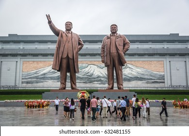 Pyongyang, North Korea - August 5th 2016 - Locals and tourist in front of the Northern Korea leader statue in a cloudy day. Pyongyang, North Korea