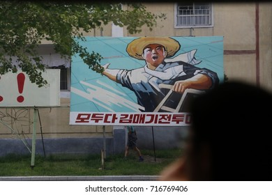 PYONGYANG, NORTH KOREA (DPRK) - JUNE 30, 2014:  Propaganda poster by the side of the road in North Korean capital.