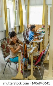 Pyongyang, North Korea - July 29, 2014: Pyongyang Embroidery Institute. Korean woman embroiders a picture at the Pyongyang Embroidery Institute.