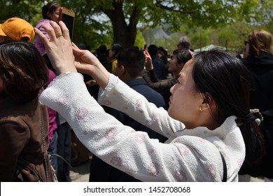 Pyongyang, North Korea - May 1, 2019: Local girl takes pictures with mobile phones on the Pyongyang street