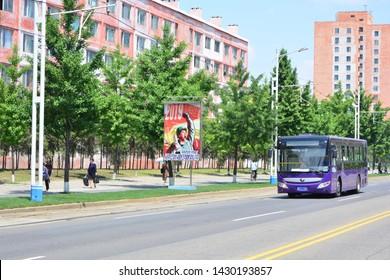 PYONGYANG, NORTH KOREA - MAY 31TH, 2019: Bus and a communist propaganda at the streets of Pyongyang, the capital of North Korea, on May 31th, 2019