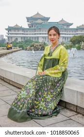 Pyongyang ,North Korea-August15,2016:Asian woman wears North Korean traditional costume  sit in front of the fountain .