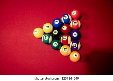 A Pyramid of Billiard Balls on a Red Table