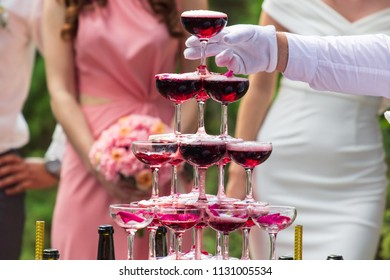 A pyramid of champagne glasses with a rose petals