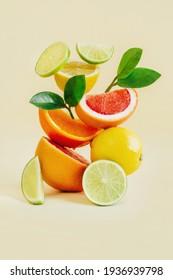 pyramid of citrus fruits grapefruit, orange, lemon, lime on yellow background