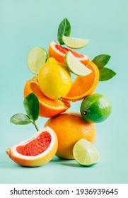 pyramid of citrus grapefruit, lemon, orange and lime decorated with leaves on a blue background