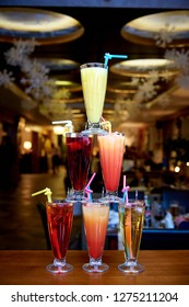 The pyramid of cocktails on the bar on a blurred background of the restaurant.