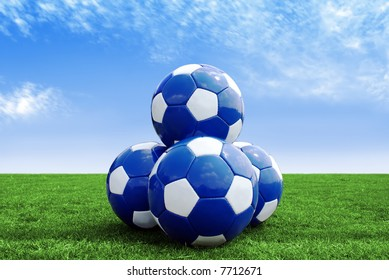 Pyramid of four soccer balls on green field against a blue sky with clouds