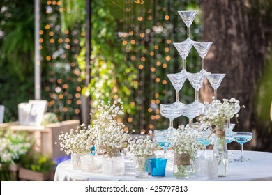 Pyramid of glasses of champagne at outdoor garden in wedding ceremony