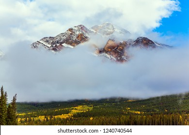 Pyramid Mountain glistens in the sun. The morning fog beautifully rises to the sky. The concept of ecological and photo tourism. Rocky Mountains, Canada