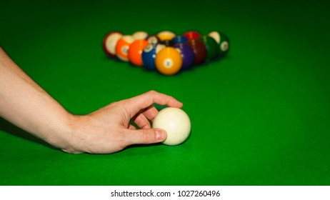 Pyramid off billiard balls ready for a game with a male hand in front.
