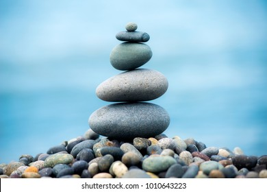 Pyramid of pebbles on the beach.Waves in background,Turkey