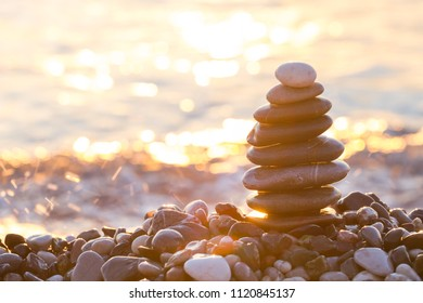 Pyramid of pebbles with sunrise on the sea