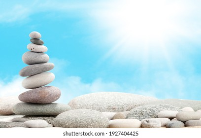 Pyramid of sea pebbles in front of sunny sky. Life balance and harmony concept