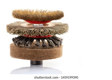 Pyramid from a set of wire abrasive grinding brushes for coarse processing and polishing of wood and metal and felt polishing wheels on a white background, isolated, close-up.