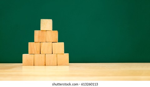 Pyramid shape build from wood cube on wooden table with green blackboard at background,Banner mock up for display or montage of design,Business Hierarchy development concept