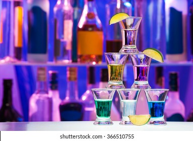 Pyramid of shot glasses with drinks and lime
