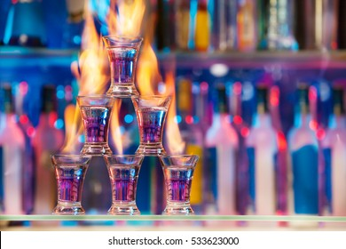 Pyramid of shot glasses with flaming cocktails