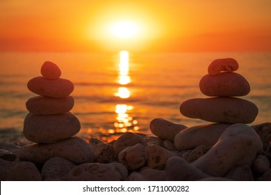 Pyramid of the small pebbles on the beach. Stones, against the background of the sea shore during sunset