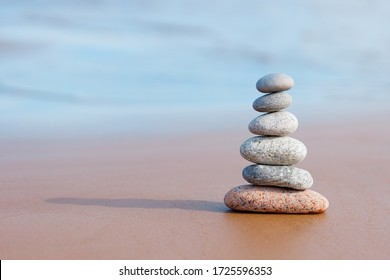 Pyramid stones balance on the sand of the beach. The object is in focus, the background is blurred.