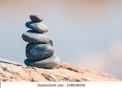 Pyramid of stones installed on large stone. House for the soul and prayer