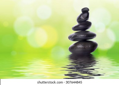 Pyramid of the stones isolated on green bokeh background. Spa Concept.