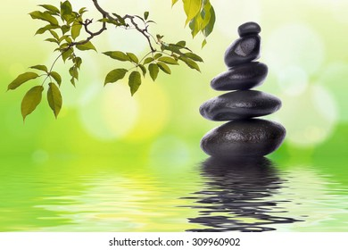 Pyramid of the stones isolated and tree branches with green leaf or Zen pebbles balance on green bokeh background. Spa Concept.