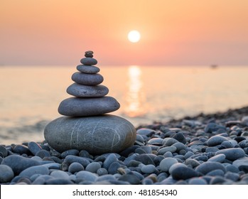 Pyramid of stones for meditation lying on sea coast at sunset