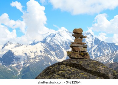 pyramid of stones and mountains with blue cloudy sky in the background