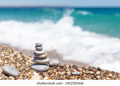 Pyramid of stones near the ocean. Obo from pebbles. Stone tower on the beach, blue waves behind. Balance, peace of mind.