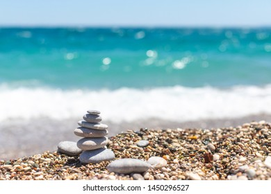 Pyramid of stones. Obo from pebbles. Stone tower on the beach against the blue sea. Balance, peace of mind, stones form a pyramid on pebble beach.