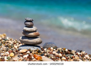 Pyramid of stones on pebble beach near the ocean. Obo from pebbles. Stone tower on the beach. Balance, peace of mind.
