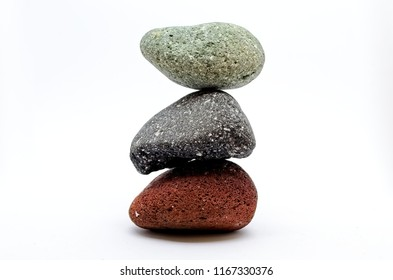 Pyramid of three colored stones over white background