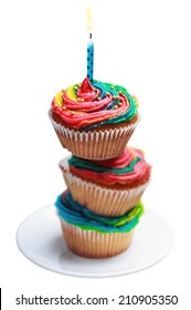 Pyramid of three colorful cupcakes with a burning candle on a plate