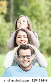 Pyramid of three family members. Cute girl above beautiful woman and handsome man in glasses. Green trees in background. Happy kid and parents having fun in park. Portrait of people outdoors.