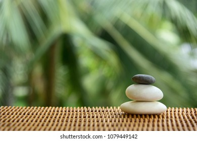 Pyramid of three smooth pebbles on the rattan table. Balanced Zen stones on blurred tropical background.